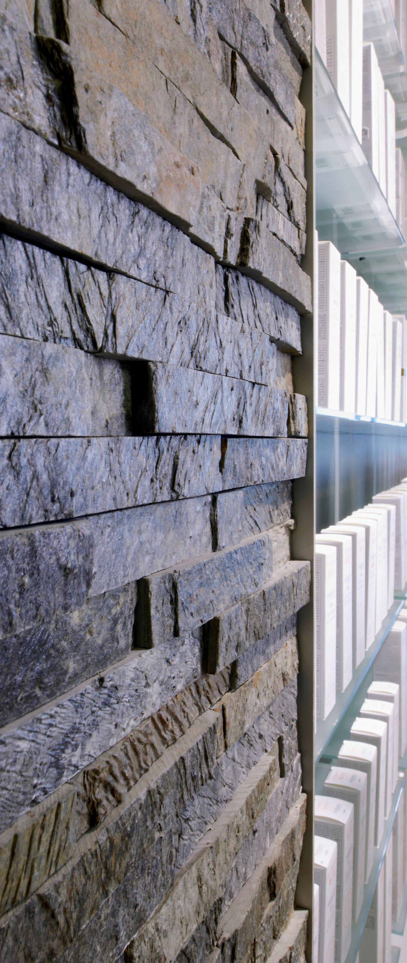 Das Freiwahlregal mit satinierten Glasböden der Apothekeneinrichtung ist in eine Natursteinwand integriert