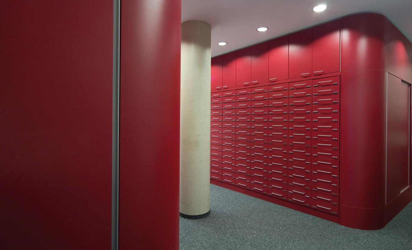 Die Schubschrankanlage wurde passend zur Apothekeneinrichtung mit rotem Schichtstoff überzogen – © 2020 huebbers.com